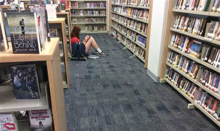 HS Girl reading in the stacks.